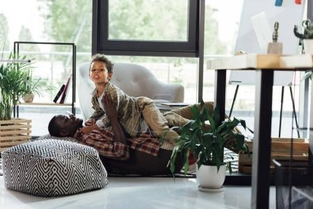 Photo for Father and son cuddling in modern office - Royalty Free Image