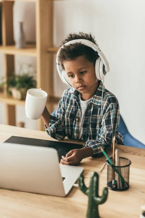boy with headphones looking at laptop