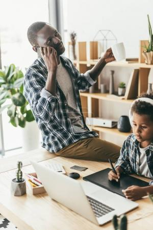 father talking by phone while son drawing