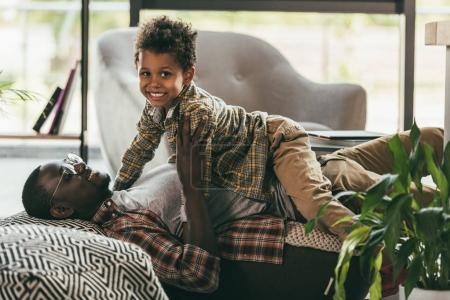 Photo for Happy african american father with cute smiling son having fun together in office - Royalty Free Image