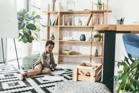 Photo pour Adorable garçon afro-américain assis sur le plancher dans le Bureau de dessin - image libre de droit