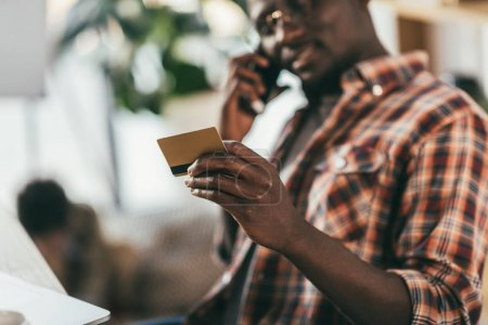 Man with credit card talking on smartphone