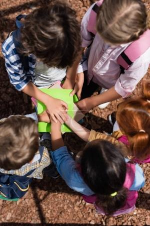 kids stacking hands above books