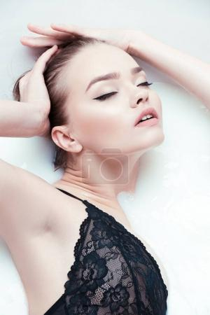 young woman having bath with milk