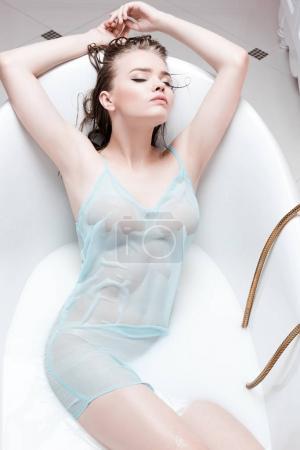 Woman in lingerie lying in bath tube