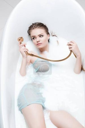 woman with shower head in bath tube
