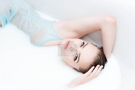 Woman having bath with milk