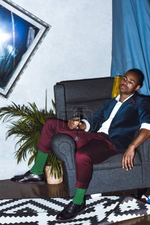 man sitting in armchair on party