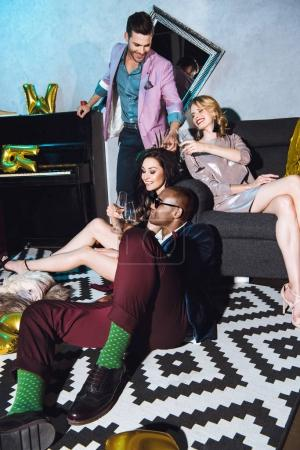 Photo for Group of friends on party sitting on floor and celebrating - Royalty Free Image
