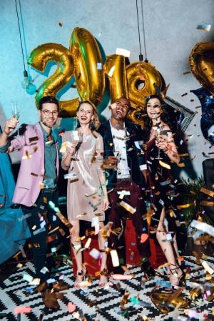 Photo for Group of friends celebrating new year together with confetti - Royalty Free Image
