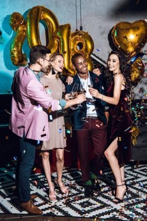Photo pour Groupe d'amis célébrant le Nouvel An ensemble dans loft intérieur - image libre de droit
