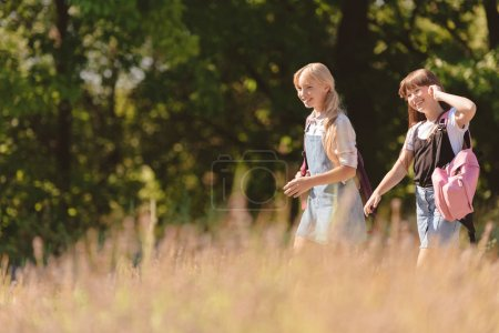 Photo for Side view of beautiful smiling teenage girls with backpacks walking in park - Royalty Free Image