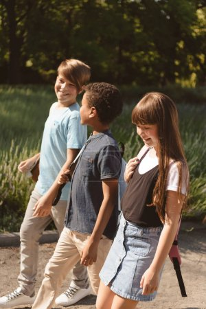 Photo for Side view of smiling multiethnic teens walking in park - Royalty Free Image