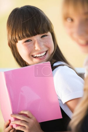 Photo for Beautiful happy teenage girl holding book and smiling at camera - Royalty Free Image