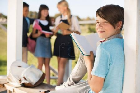 Photo for Smiling teenage boy reading book while classmates standing behind outdoors - Royalty Free Image