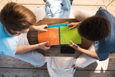 Photo pour Vue aérienne de deux adolescents avec des livres étudiant ensemble sur banc - image libre de droit
