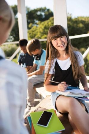 Smiling teenager studying with books
