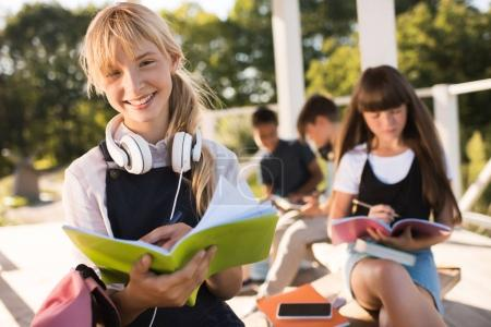 Photo for Cute teenage girl with headphones smiling at camera while classmate studying behind outdoors - Royalty Free Image