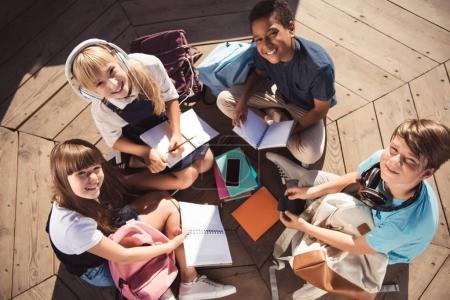 Photo for Overhead view of cheerful multiethnic teens studying together and smiling at camera - Royalty Free Image