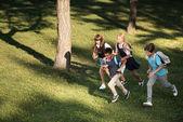 multiethnic teenagers running in park