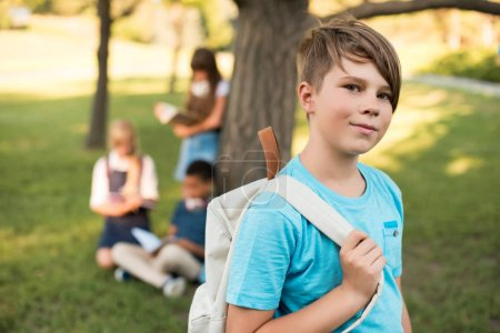 Photo for Portrait of cute smiling teenage boy holding backpack and looking at camera outdoors - Royalty Free Image