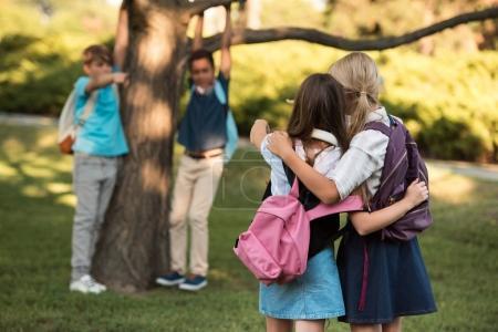 Photo pour Vue arrière du écolières adolescentes avec sacs à dos, pointant avec doigts à garçons - image libre de droit