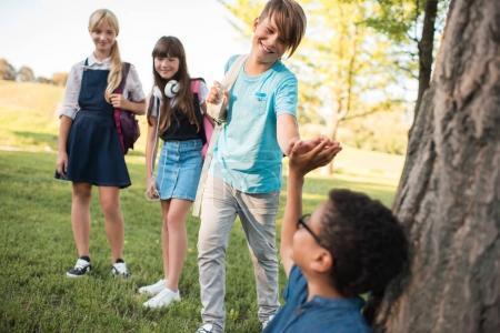 Photo pour Souriant multiethnique adolescents réunion et donnant cinq dans le parc - image libre de droit