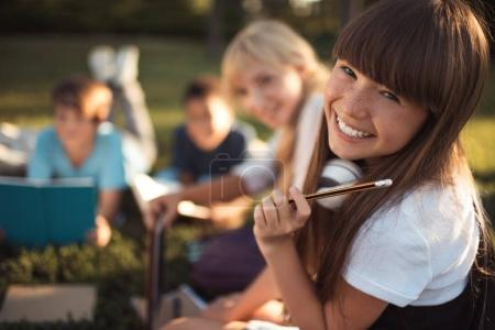 Photo for Portrait of beautiful happy teenage girl holding pencil and smiling at camera - Royalty Free Image