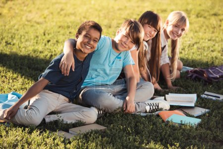 Multiethnic teenagers studying in park