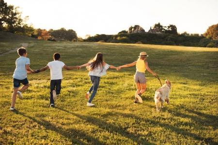 Photo pour Vue arrière des adolescents heureux tenant la main et courant avec le chien dans le parc - image libre de droit