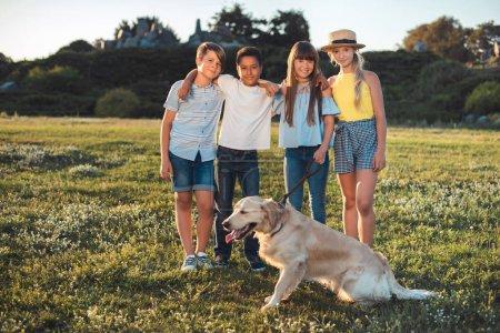 Photo pour Joyeux adolescents multiethniques debout embrassant et souriant à la caméra tout en passant du temps avec le chien dans le parc - image libre de droit