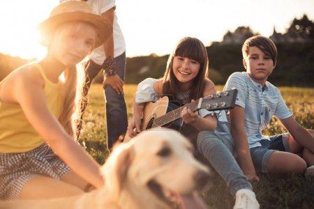 Foto de Adolescentes felices multiétnicos con el perro y la guitarra en el Parque - Imagen libre de derechos