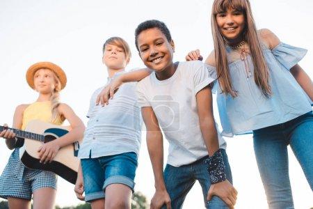 Photo pour Groupe d'adolescents multiethniques heureux avec guitare souriant à la caméra à l'extérieur - image libre de droit