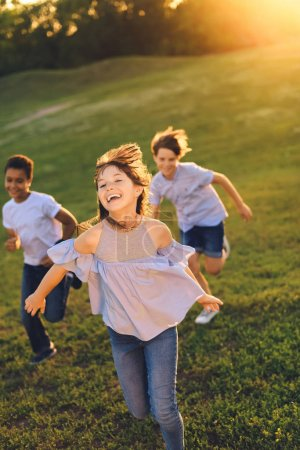 Photo for Happy multiethnic teens running together in park - Royalty Free Image