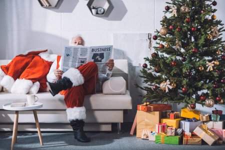 Photo for Obscured view of santa claus reading business newspaper while sitting on sofa - Royalty Free Image
