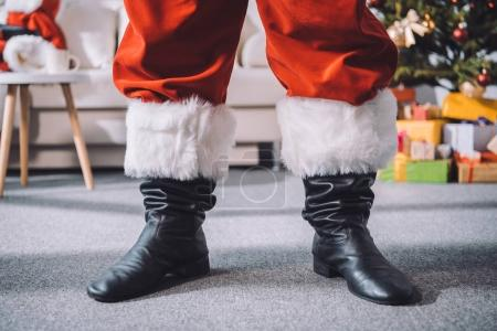Photo for Cropped shot of santa claus in black boots standing in room - Royalty Free Image