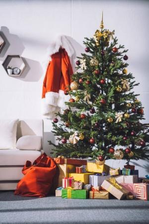 Photo pour Divers cadeaux enveloppés couchés sous l'arbre de Noël dans la chambre - image libre de droit