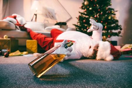Photo for Selective focus of santa claus holding bottle of whiskey while lying on floor - Royalty Free Image