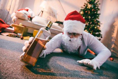 Foto de Enfoque selectivo de borracho mala santa celebración botella de whisky - Imagen libre de derechos