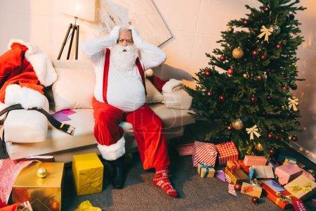 Foto de Impactado santa claus sentado en el sofá en la habitación con árbol de Navidad y regalos envueltos - Imagen libre de derechos