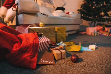 Photo for Close up view of various wrapped christmas gifts and letter for santa in bag - Royalty Free Image