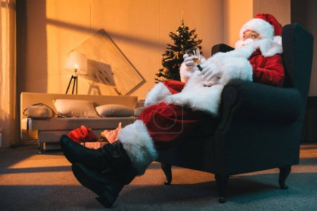 Photo for Santa claus with glass of whiskey and cigar in hands resting in armchair - Royalty Free Image