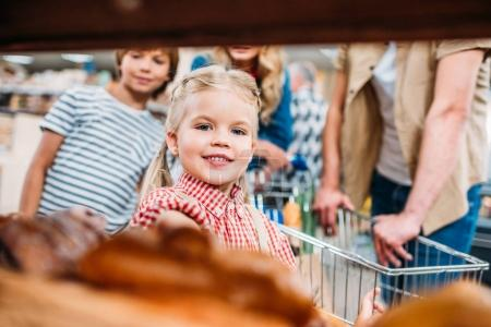 girl with family in supermarket
