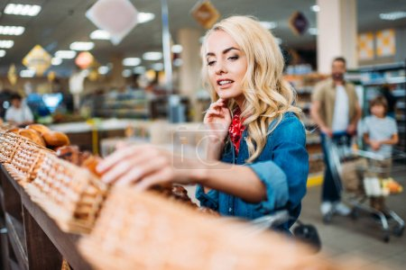 Photo for Selective focus of young woman choosing pastry in supermarket - Royalty Free Image