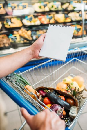 Man with empty notebook in supermarket