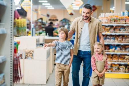 Photo pour Père avec des petits enfants mignons choisissant des marchandises au supermarché - image libre de droit
