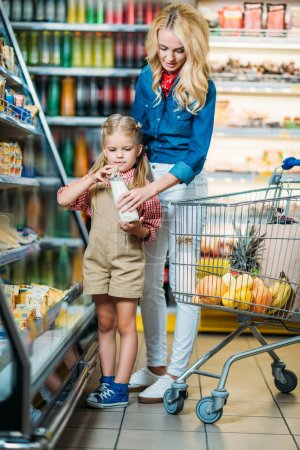 Mother and daughter buying milk