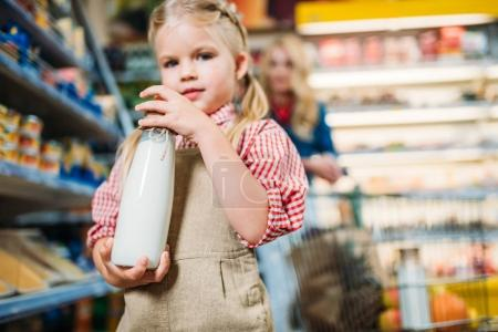 girl holding bottle of milk