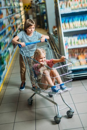Kids with shopping cart in supermarket