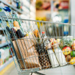 Selective focus of shopping cart with purchases in...